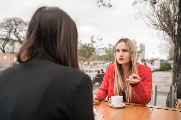 Due amici arrabbiati che discutono mentre sedendosi alla caffetteria.
