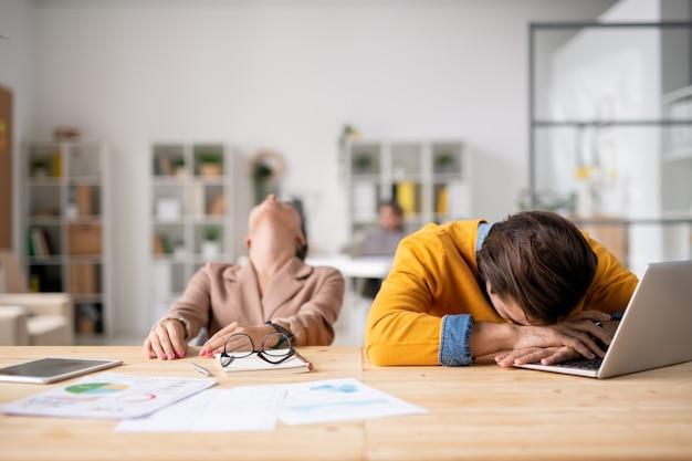 2人のイライラしたサラリーマンが机のそばに座って、そのうちの1人がラップトップのキーパッドに横になっていて、同僚が頭を後ろに投げている