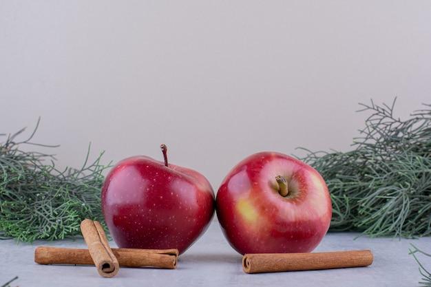 Два яблока и палочки корицы среди сосновых веток на белом фоне.