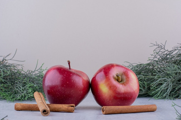 Two apples and cinnamon sticks among pine branches on white background.