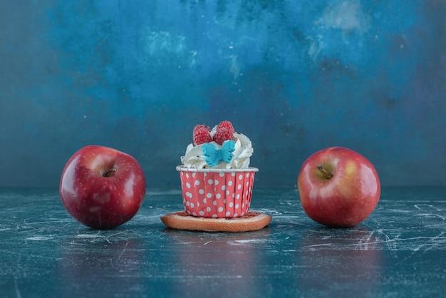Due mele e un cupcake su una fetta di pompelmo su sfondo blu. foto di alta qualità