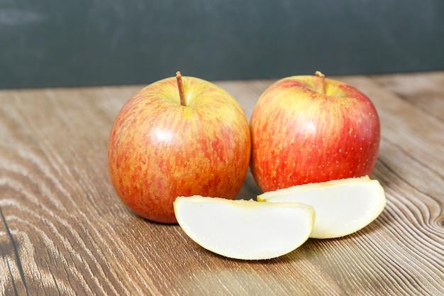 Два яблока на деревянном столе и кусочки