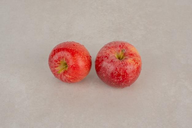 베이지 색 테이블에 두 개의 사과입니다.