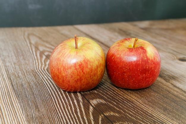 Два яблока на деревянном столе с черным фоном.