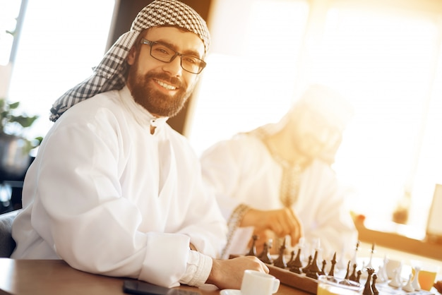 Two arab businessmen playing chess at table at hotel room.
