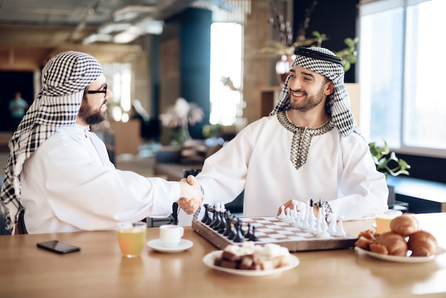 Two arab businessmen shake hands behind chess board.