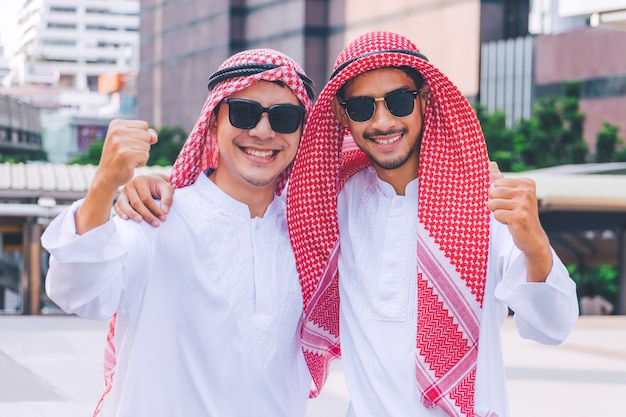 Two arab businessmen standing by raising both hands up in city