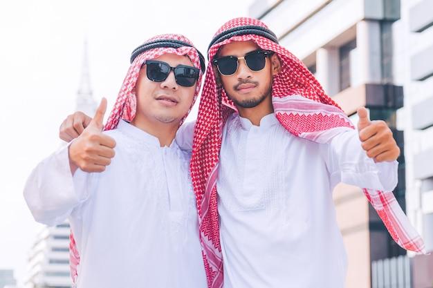Два арабских бизнесменов стоят, подняв обе руки в городе