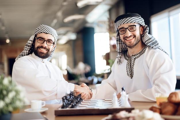 チェスをする前に2人のアラブが握手します。