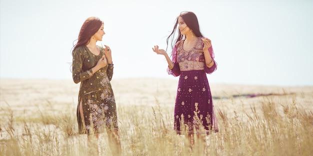 砂漠での旅行を疲れ果てた後、国民服を着た2人のアラビア人女性がオアシスを見つけました。