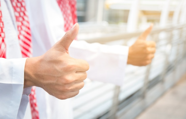 Two arabic businessman showing thumbs up