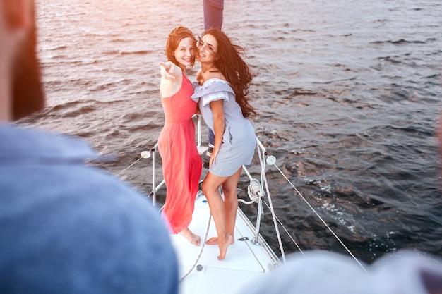 Две возбужденные молодые женщины стоят и смотрят на мужчин. девушка в красном платье указывает на него