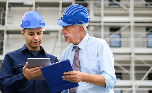 Two architect developers reviewing building plans at construction site using a tablet