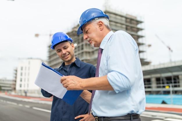 두 명의 건축가 개발자가 건설 현장 앞에서 건물 계획을 검토하고 있습니다.
