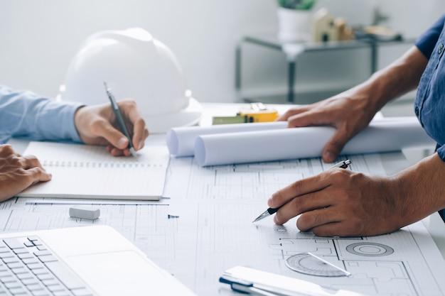 Два архитектора обсуждают проект и работают над чертежом на строительной площадке в офисе