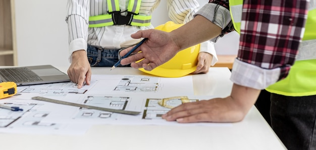 Two architect-engineers are consulting to modify the blueprints of the contracted house, they have a meeting to inspect the house designs before meeting with the client. home design ideas.