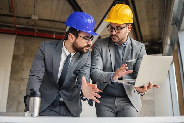 Два архитектора в строительстве в процессе строительства говорят и проводят мозговой штурм об инновациях в своем проекте.
