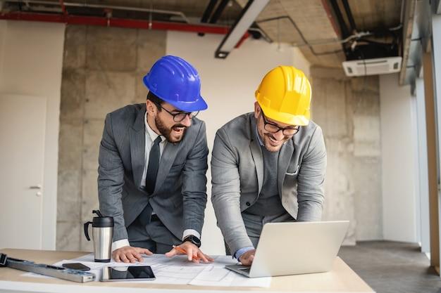 Два архитектора смотрят на ноутбук и работают над большим проектом