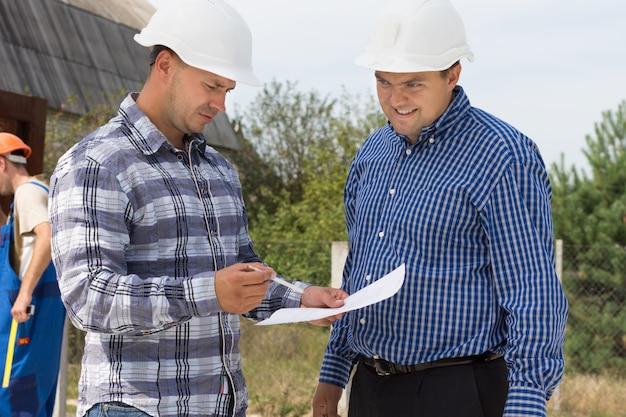 2人の建築家が、バックグラウンドで作業している作業員と一緒に建築現場で話しているときに、ハンドヘルドドキュメントの仕様を確認しています