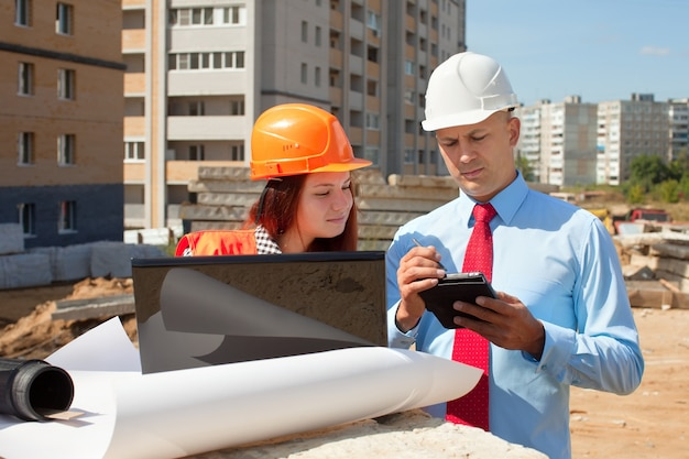 Two architects  in front of building site