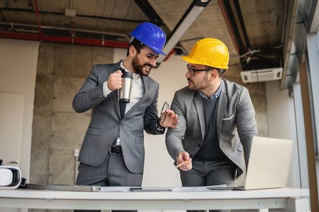 Два архитектора стоят в здании в процессе строительства и говорят о большом проекте.
