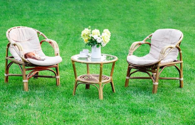 두 개의 안락 의자, 더운 여름날 휴식을 위해 야외 잔디 잔디밭에 나무 정원 가구. 자연 속에서 두 개의 의자, 꽃병과 고양이 꽃 정원 풍경. 공원 카페에서 쉬십시오. 뒤뜰 외관.