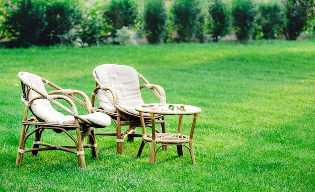 2개의 안락 의자, 야외 잔디 잔디밭에 있는 나무 정원 가구로 더운 여름에 휴식을 취하실 수 있습니다. 자연 속에 두 개의 의자가 있는 정원 풍경. 공원 카페에서 휴식. 뒤뜰 외관입니다. 아무도.