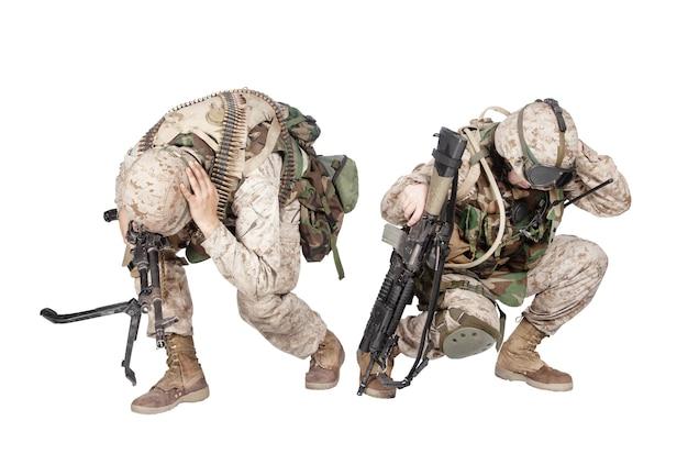 위장복을 입은 두 명의 군인, 돌격 소총과 기관총으로 무장하고 땅에 웅크리고 헬멧을 들고 흰색 스튜디오 촬영에 격리된 손으로 귀를 덮고 수류탄이나 폭탄 폭발