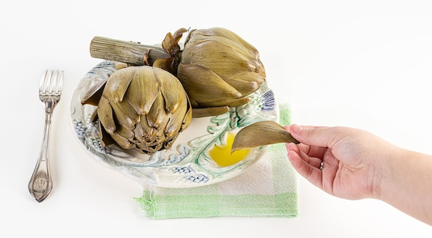 Two artichokes cooked in a plate with oil