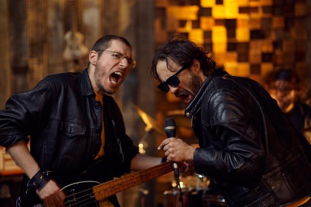 マイクで2人のアーティスト、バーのステージで歌を演奏。ロックバンドの演奏、ガレージでのコンサートの繰り返し、楽器を持った男、ライブサウンドパフォーマー