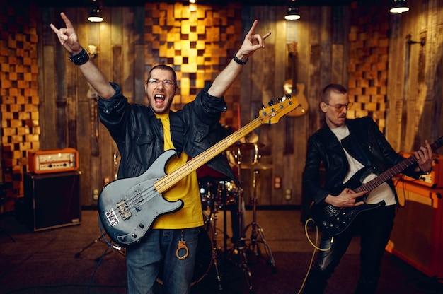 На сцене выступают два артиста с электрогитарами. выступление рок-группы или повторение в гараже, человек с музыкальным инструментом, живой звук