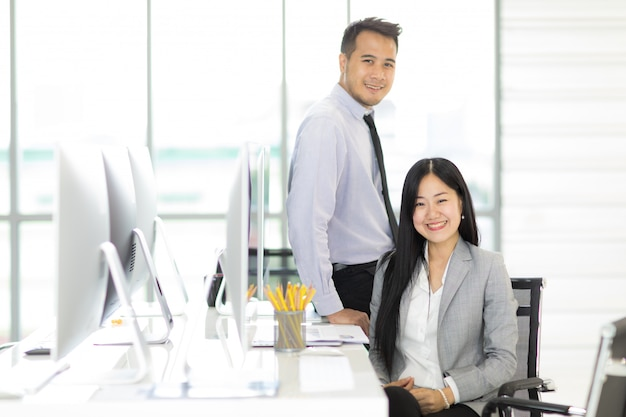 Two asain businessman and businesswoman relaxing together in office.