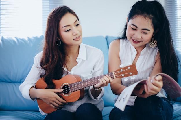 Две азиатские женщины весело играют на гавайской гитаре и улыбаются дома на время отдыха