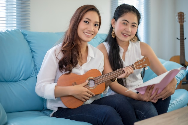 Two asia women are having fun playing ukulele and smiling at home for relax time