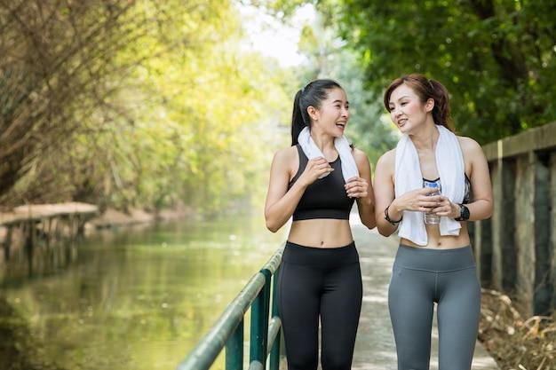 新鮮な自然の背景と一緒に朝ジョギングやランニングで屋外で2人のアジアの大人の女性