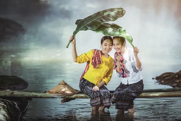 Two asian beautiful girl plays the water in the river at thailand.