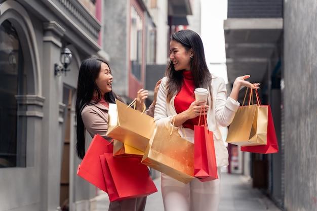 쇼핑몰 배경 위에 도시에서 쇼핑백을 든 두 명의 아시아 미녀