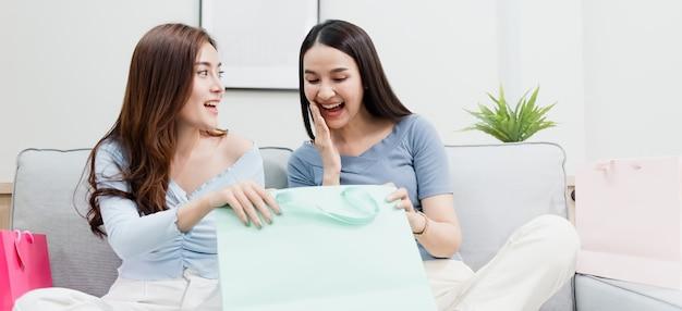 幸せな笑顔で紙袋を開ける2人のアジアの美人が新しい通常のオンラインビジネスである自宅からのショッピング体験
