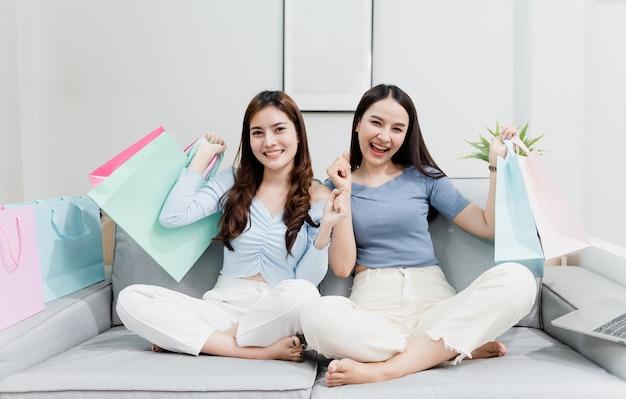 幸せな笑顔で紙袋を持ち上げる2人のアジアの美人が自宅からのショッピング体験で新しい通常のオンラインビジネスであること