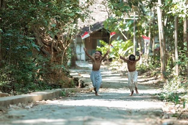 Два азиатских мальчика бегают без одежды, гоняясь друг за другом, держа в руках красно-белый флаг