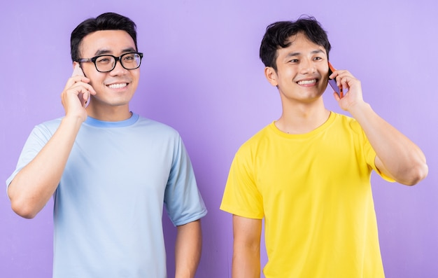 Two asian brothers using cell phones on purple background