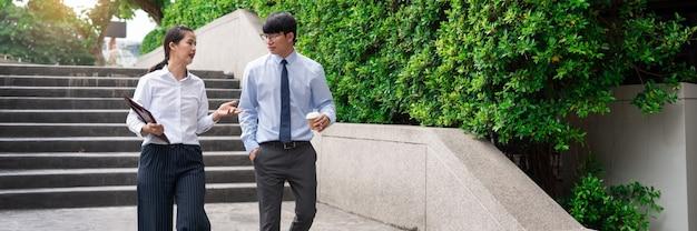 사무실 건물 외부의 두 아시아 비즈니스 동료가 서로 토론하고 작업에 대해 설명합니다.