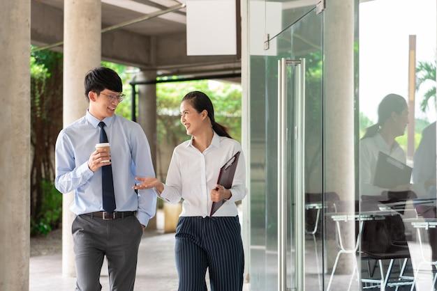 オフィスビルの外にいる2人のアジア人ビジネスの同僚が、お互いに仕事について話し合い、コメントしています。