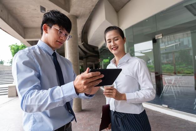 オフィスビルの外にいる2人のアジア人ビジネス同僚が、お互いに仕事について話し合い、コメントしています。