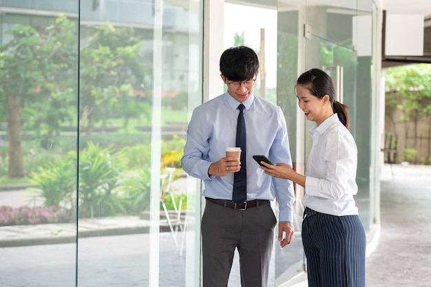 Two asian business coworkers outside office buildings discuss and commenting work to each other.