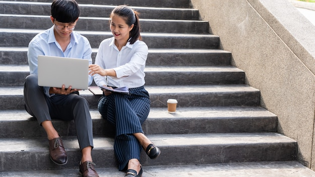 階段に座っている2人のアジアのビジネス同僚がラップトップで仕事について話し合い、コメントします