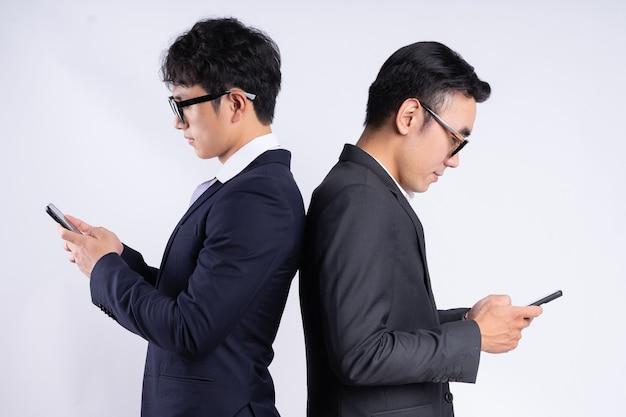 お互いに寄りかかって、白い背景の上の携帯電話を使用して2人のアジアのビジネスマン