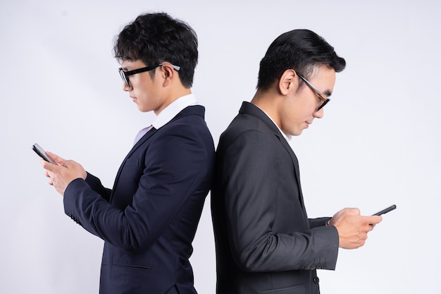 Two asian business men leaning against each other and using mobile phones on a white background