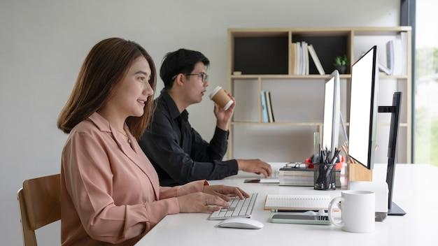 두 명의 아시아 사업가가 현대 사무실에 함께 앉아 컴퓨터 작업을 하고 있습니다.