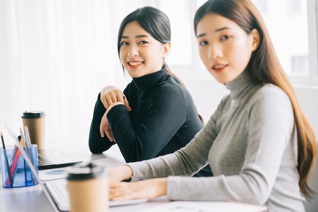 2人のアジアのビジネスウーマンがオフィスに集まっています